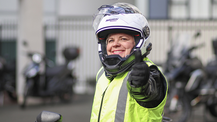 A female rider wears a helmet, gloves, jacket and hi-vis vest.