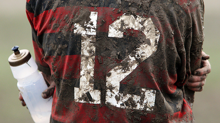 Muddy rugby player with drink bottle