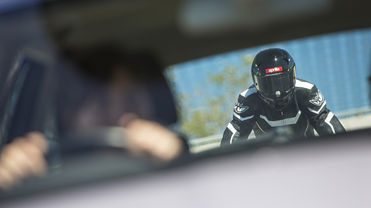 Driver sees motorcyclist in rear-view mirror