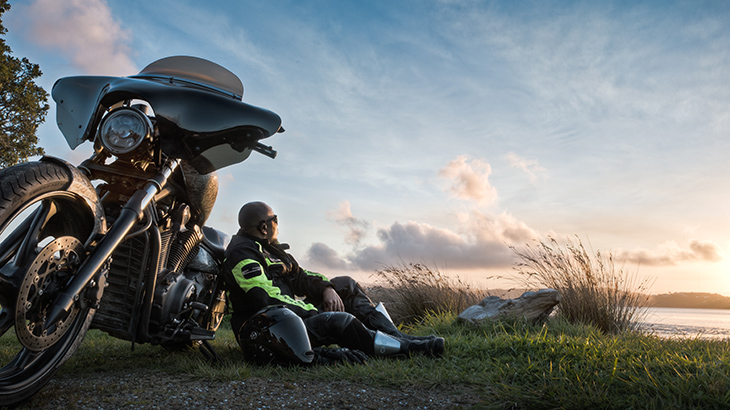 Motorcyclists sits on grass, leaning against his bike.