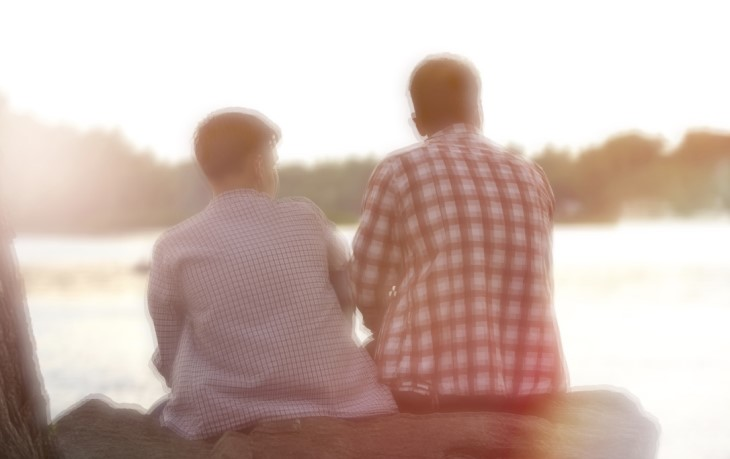 Father and son, sitting by a lake talking