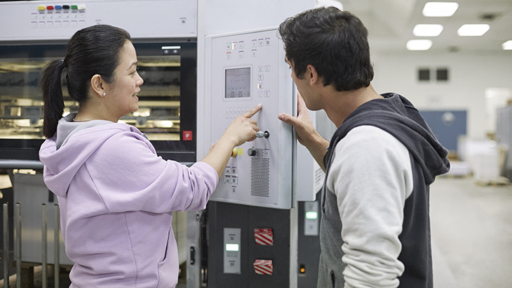 A worker is instructing another worker on how to use a manufacturing machine