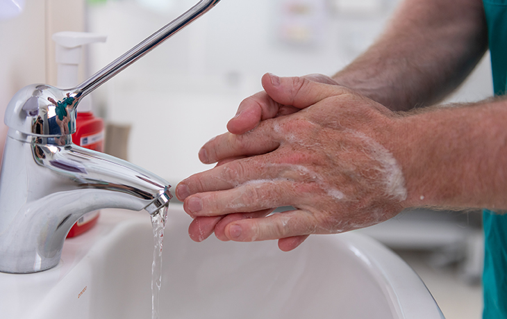 A person washes their hands with soap and water