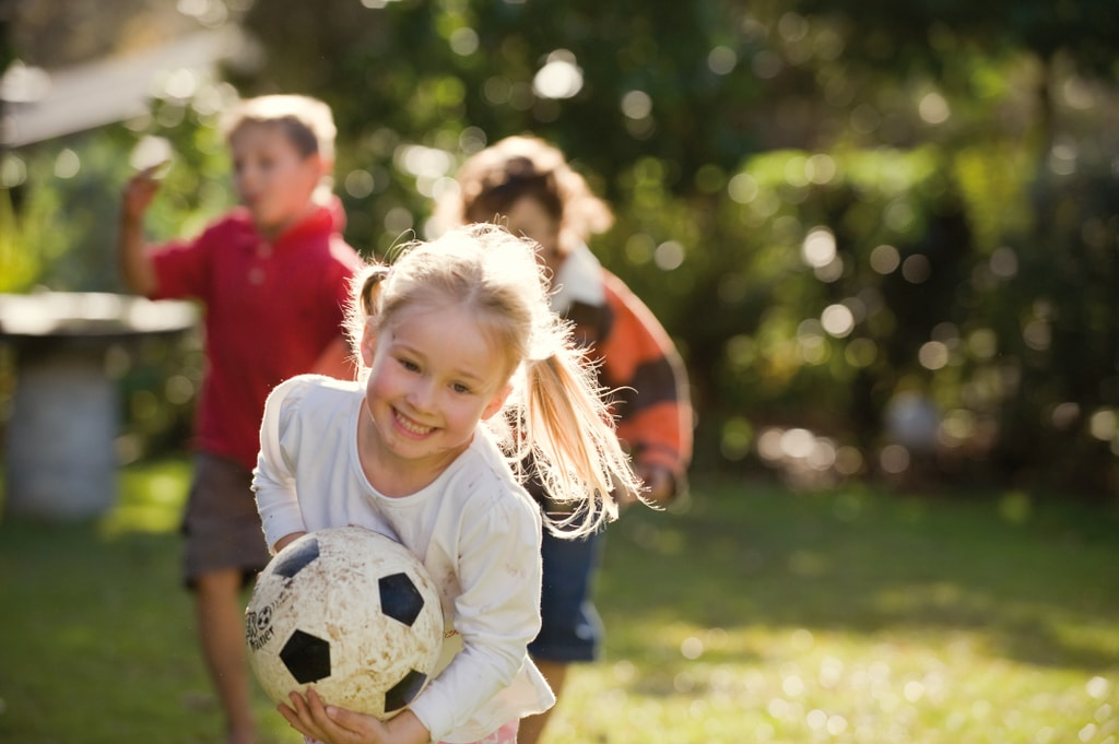 Kids playing in garden with soccer ball